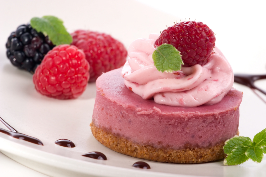 Delicious raspberry cheesecake served with fresh raspberries, blackberries, mint and chocolate syrup.